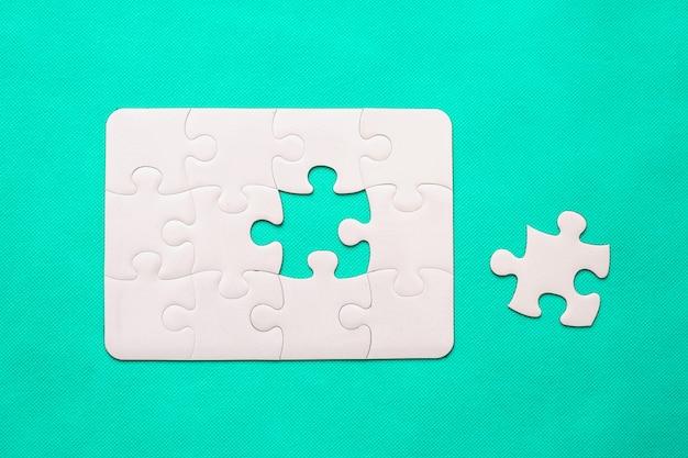Jigsaw puzzle con pezzo mancante su sfondo di menta vista dall'alto