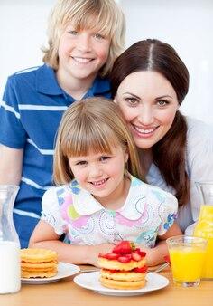 Jolly madre e i suoi figli mangiano cialde con fragole