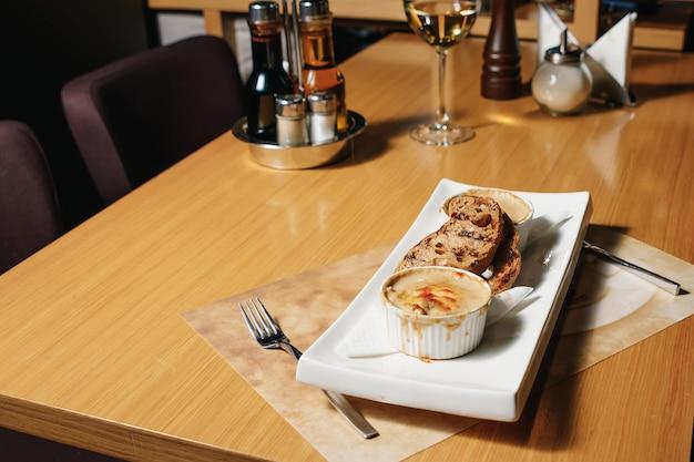 Julien in un kokotnitsa bianco e ciabatta su un tavolo in un ristorante.