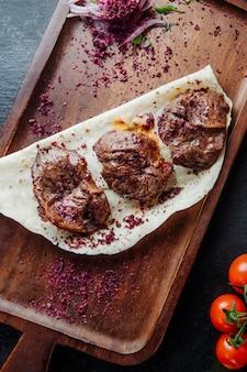 Kabab di carne servito con cipolla crespino e pomodori