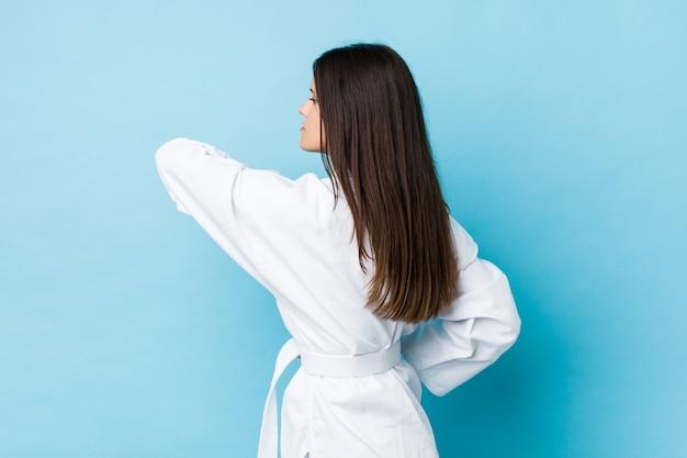 Karatè di pratica della giovane donna caucasica isolato su una parete blu