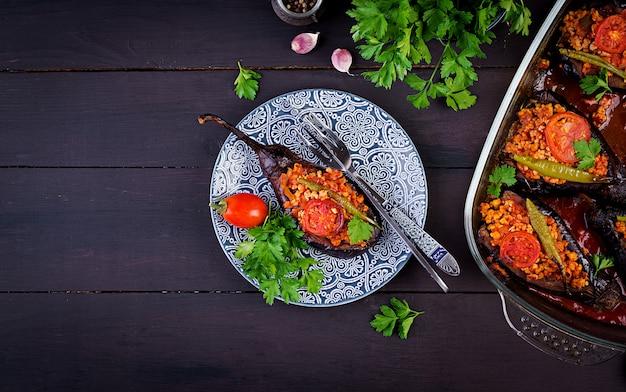 Karniyarik - pasto turco tradizionale di melanzane alle melanzane. melanzane ripiene con carne macinata e verdure al forno con salsa di pomodoro