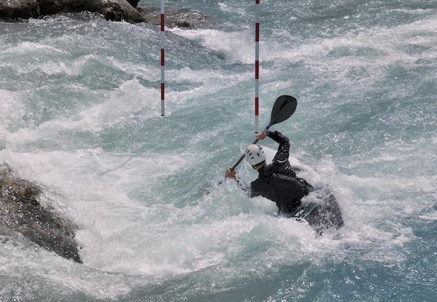 Kayak della canoa che attraversa porta rossa su acqua bianca