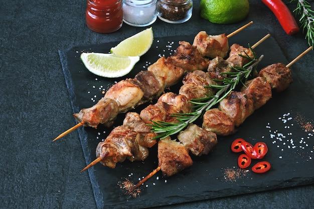 Kebab appetitoso con spezie, peperoncino e lime. spiedi fragranti del maiale su un bordo di pietra.