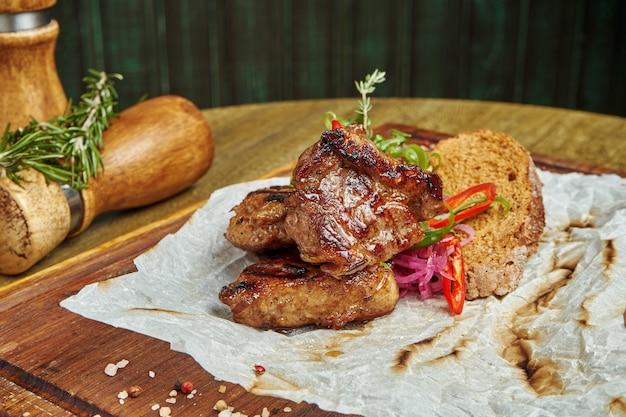 Kebab appetitoso della carne di maiale con le spezie e le cipolle su un vassoio di legno su superficie di legno. shahlik. porzione di carne alla griglia. primo piano, messa a fuoco selettiva