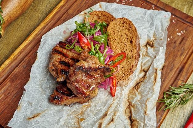 Kebab appetitoso della carne di maiale con le spezie e le cipolle su un vassoio di legno su superficie di legno. shahlik. porzione di carne alla griglia. vista dall'alto, piatto