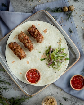 Kebab caucasico del barbecue nel lavash con insalata di erbe.
