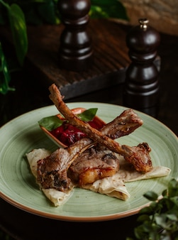 Kebab di agnello con salsa di pomodoro all'interno del piatto in ceramica verde