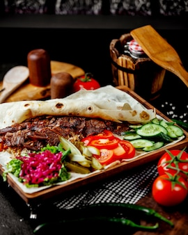Kebab di agnello in focaccia servito con sottaceti ed erbe di cetriolo al pomodoro