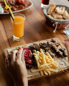 Kebab di agnello su spiedini di bambù servito con patatine fritte, cavolo sottaceto, insalata