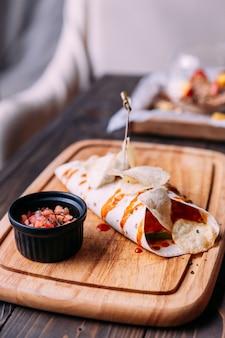 Kebab di carne con patatine fritte con salsa e servito con insalata di pomodori sul piatto di legno
