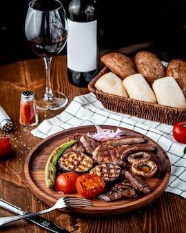 Kebab di carne con verdure su tavola di legno