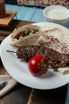 Kebab di carne in lavash con pomodoro, erbe e spezie.