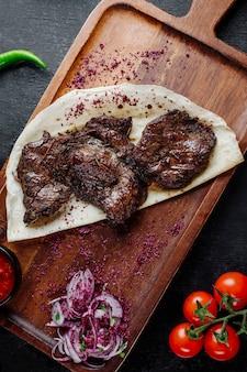 Kebab di carne servito con cipolle e crespino