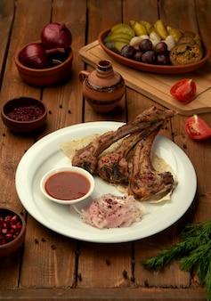 Kebab di costolette di agnello servito con salsa di pomodoro e anelli di cipolla fresca