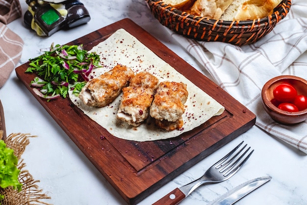 Kebab di lula della carne di vista laterale sul pane della pita con le erbe e le cipolle su un bordo