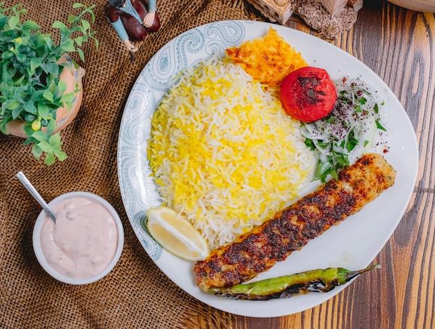 Kebab di lula di pollo vista dall'alto con verdure grigliate di riso e cipolle