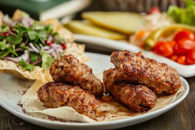 Kebab di lula servito con trito, cipolla e verdure