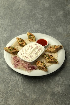 Kebab di lule avvolto in focaccia, servito con yogurt e salsa di pomodoro