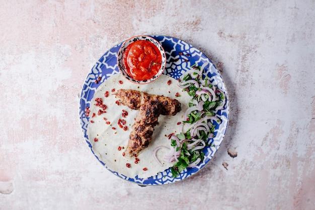 Kebab di lule azero alimentare con erbe e salsa barbecue all'interno del piatto decorativo.