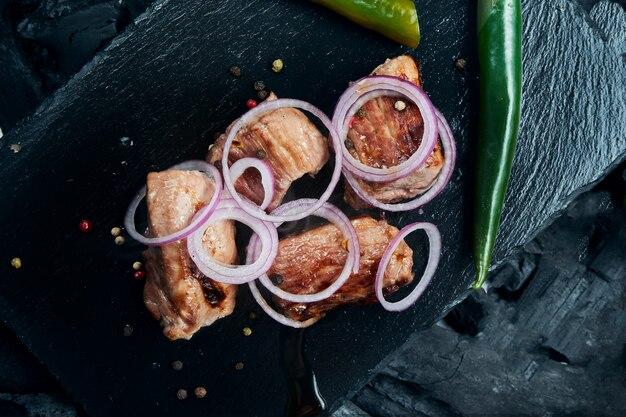 Kebab di maiale appetitoso con spezie e cipolle su un vassoio di ardesia nera su una superficie di carbone. shahlik. chiuda sulla porzione di carne alla griglia