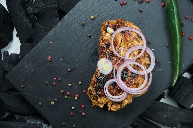 Kebab di manzo appetitoso con spezie e cipolle su un vassoio di ardesia nera su un tavolo di carbone. shahlik. chiuda sulla porzione di carne alla griglia
