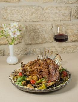 Kebab di manzo con cibo locale e vino rosso savalan.