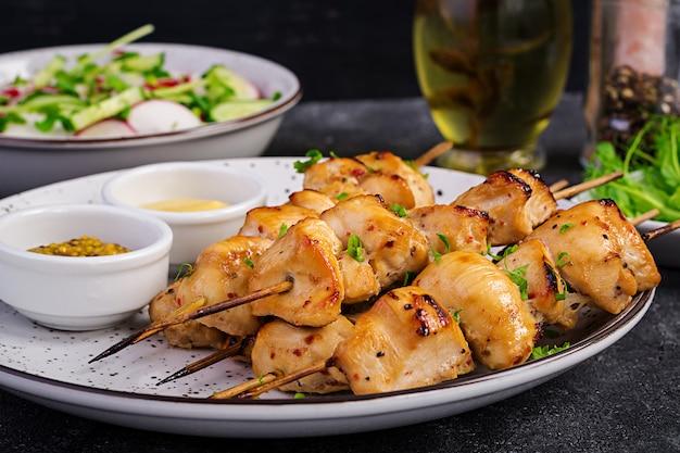 Kebab di pollo alla griglia e insalata con cetriolo, ravanello, cipolla.