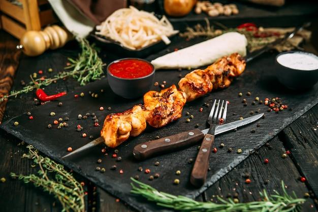 Kebab di pollo appetitoso su una superficie di legno scuro