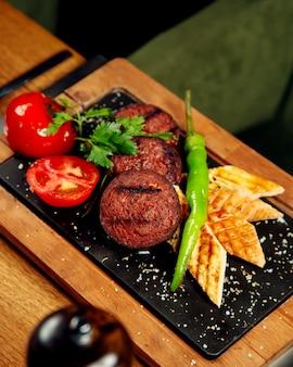 Kebab di salsiccia alla griglia con pane grigliato di pomodoro e pepe