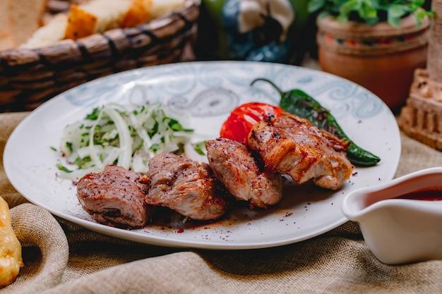 Kebab di tikya di vista laterale con la cipolla e i verdi grigliati del peperoncino del pomodoro su un piatto