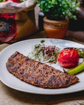 Kebab di vista laterale con la cipolla e i verdi caldi arrostiti del pomodoro del peperone verde su un piatto
