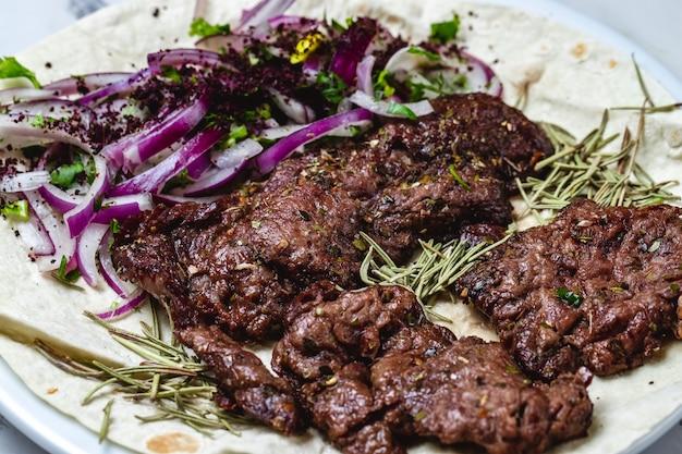 Kebab di vista laterale grigliato di carne di manzo con verdure a cipolla rossa e rosmarino su pita
