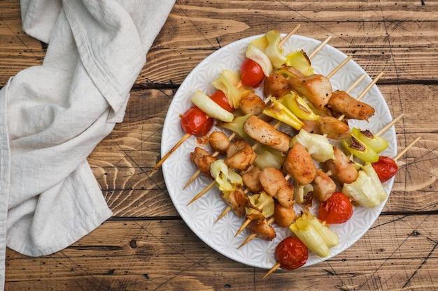 Kebab pollo, zucchine e pomodori su spiedini in un piatto.