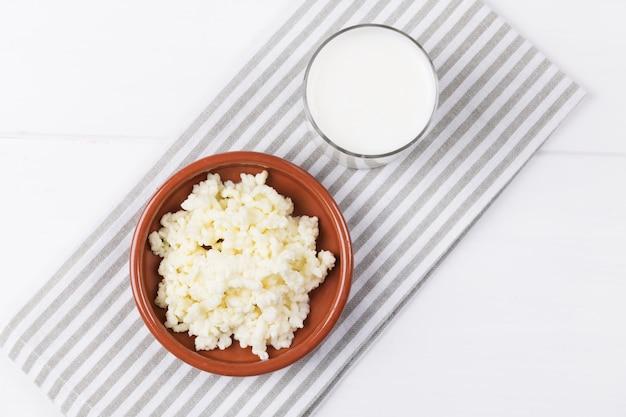 Kefir di bevande fermentate fatte in casa con chicchi di kefir in una ciotola su un tavolo bianco, concetto di cibo fermentato naturale e salute dell'intestino