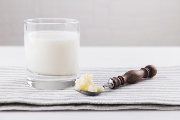 Kefir di bevande fermentate fatte in casa con chicchi di kefir in una ciotola su uno sfondo bianco, concetto di cibo fermentato naturale e salute intestinale