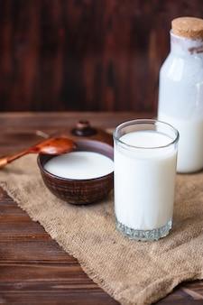 Kefir fatto in casa, yogurt con probiotici in un bicchiere sul tavolo bevanda al latte fermentata fredda probiotica cibo e bevande alla moda copia spazio stile rustico.