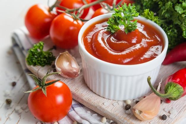 Ketchup e ingredienti su fondo di legno