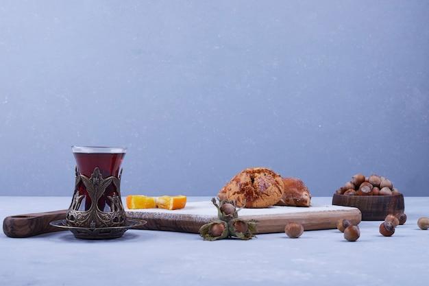Kete caucasico con zucchero in polvere servito con un bicchiere di tè sul blu
