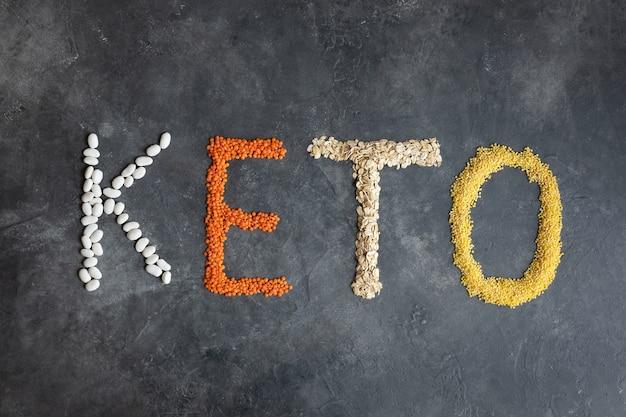 Keto parola composta da alimenti chetogenici. keto, dieta chetogenica, basso contenuto di carboidrati. vista dall'alto di cibo sano. prodotti biologici: lenticchie, farina d'avena, fagioli, miglio su un grigio scuro.