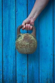 Kettlebell di ferro nella mano dell'uomo