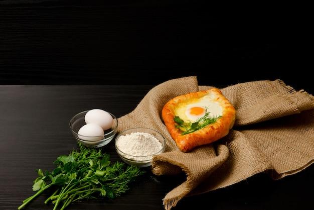Khachapuri con le uova su tela di sacco, farina, uova e prezzemolo sulla tavola nera, copyspace
