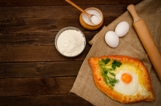 Khachapuri con le uova su tela di sacco, sale, farina e uova sulla tavola di legno, spazio per testo
