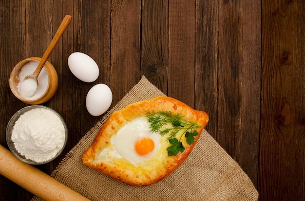 Khachapuri con le uova su tela di sacco, sale, farina, uova e prezzemolo sulla tavola di legno, copyspace