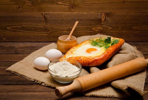 Khachapuri con le uova su tela di sacco, sale, farina, uova e prezzemolo sulla tavola di legno, vista laterale
