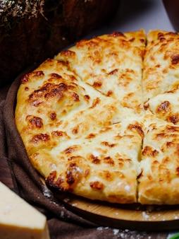 Khachapuri georgiano con formaggio fuso e affettato.