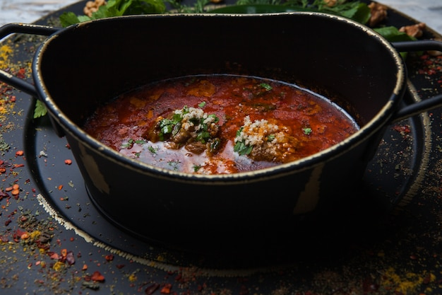 Kharcho di vista laterale con spezie e verdure nel piatto scuro