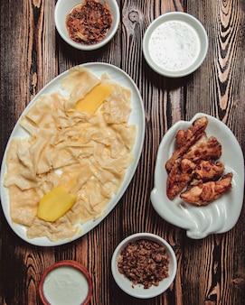 Khinkali tradizionale azero sotto forma di foglie con cipolle fritte, carne macinata e gatyg