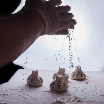 Khinkali vista laterale con farina e mano umana