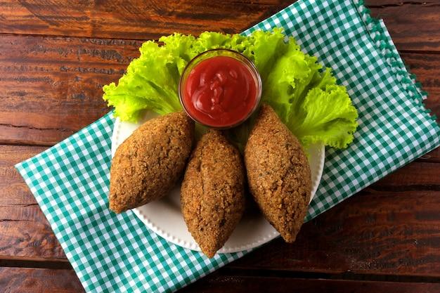 Kibbeh fritto con salsa di pomodoro su un piatto, sul tavolo in legno rustico